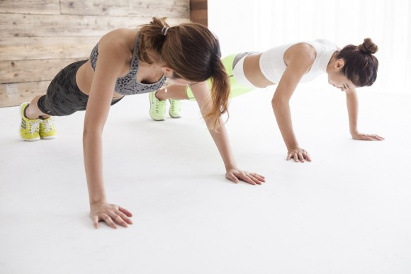 Two women are doing push-ups